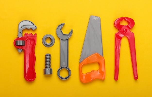黄色の背景にプラスチック製の子供の作業ツールキット。おもちゃ。上面図