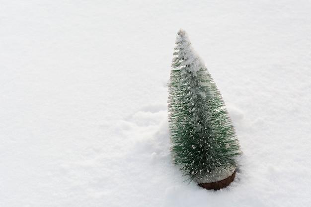 コピースペース冬の休日の背景と本物の雪の上のプラスチック製のクリスマスツリー