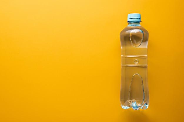 オレンジ色の背景にコピースペースとプラスチック製のきれいな水のボトル