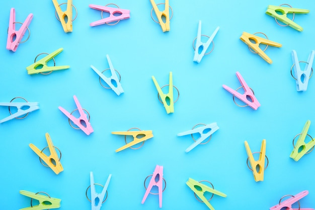 Plastic clothes pins on a blue background