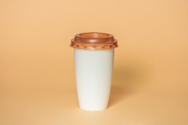 Plastic coffee cup with brown lid isolated on beige background with clipping path, mockup for your project