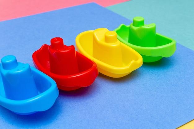 Пластиковые цветные игрушечные кораблики на ярком цветном фоне