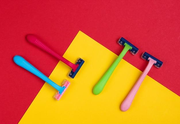 Пластиковые цветные бритвы на красно-желтом