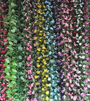 Plastic colorful flower in vertical garden background