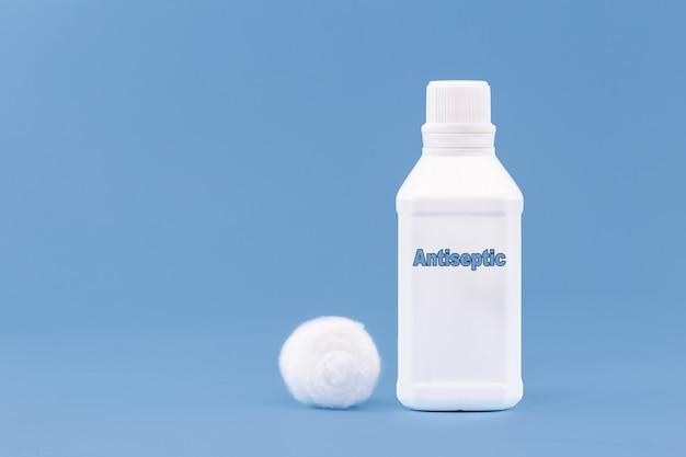 Пластиковый контейнер, бутылка с надписью на английском языке: антисептик, сплошная синяя поверхность с местом для копирования