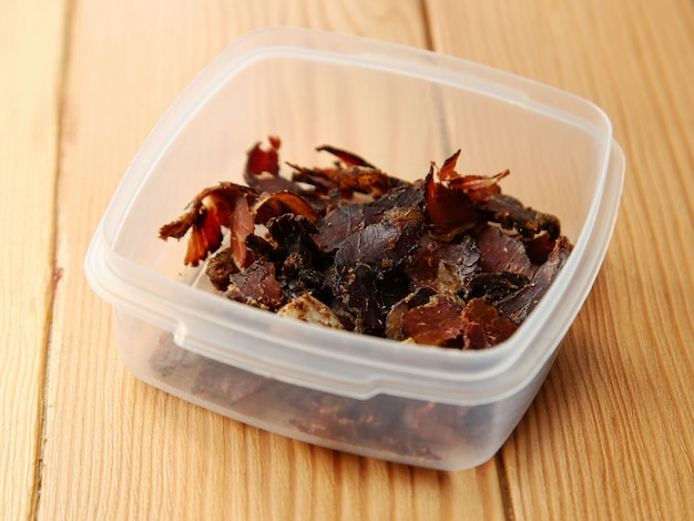 Plastic container filled with biltong snacks on a wooden surface
