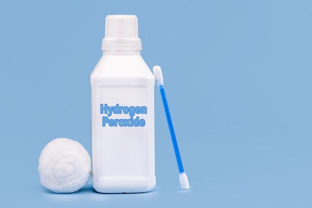 Пластиковый контейнер, бутылка с лекарством, написано на английском языке: перекись водорода, изолированный синий фон, концепция первой помощи