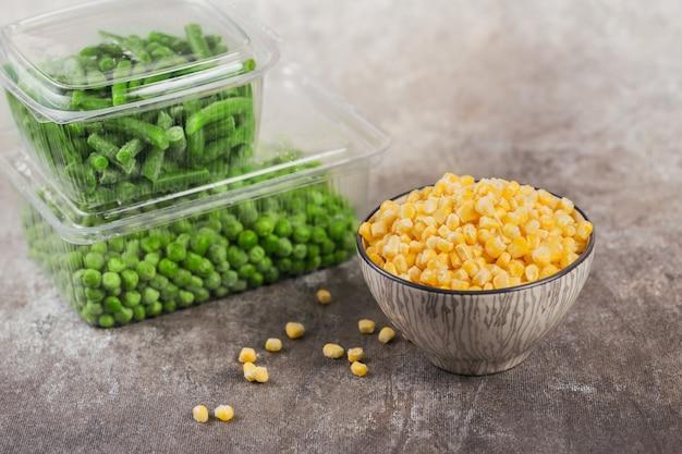 テーブルの上にさまざまな有機冷凍野菜が入ったプラスチック容器。グリーンピース、スイートコーン、カットグリーンビーンズを箱に入れて