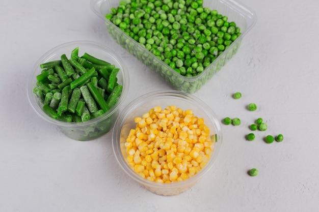 白いコンクリートのテーブルにさまざまな有機冷凍野菜が入ったプラスチック容器。グリーンピース、スイートコーン、カットグリーンビーンズを箱に入れて