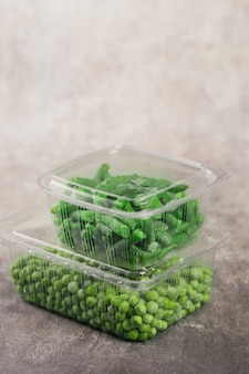 Plastic container with different organic deep frozen vegetables on a table