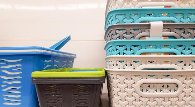 さまざまな色と価格のプラスチック容器が倉庫に置かれるか、陳列棚に保管されます。販売のための再生プラスチック、多くの選択肢。