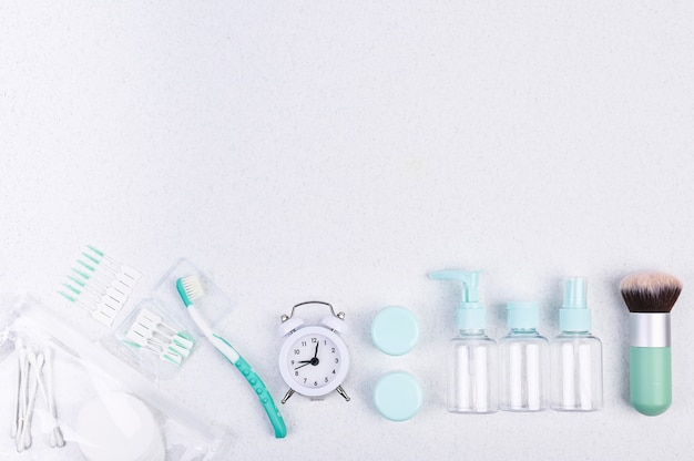 Plastic containers, toothbrush and alarm clock for travel  flat lay.