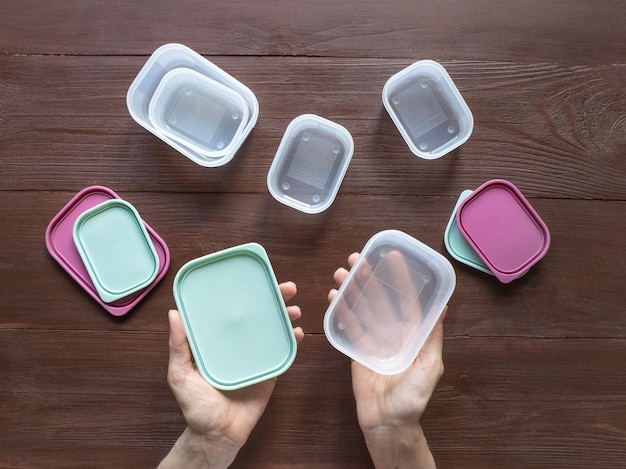 Plastic containers for transportation and storage food products laid out on a wooden table. top view
