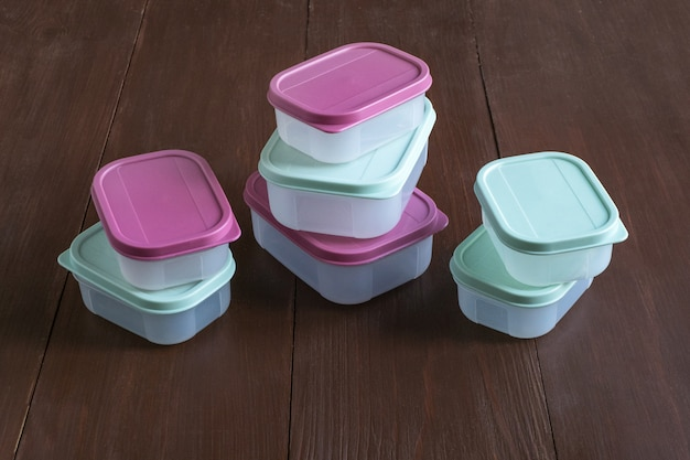 Plastic containers for transportation and storage food products laid out on a wooden table
