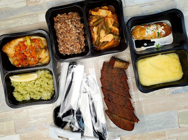 Plastic containers with delicious food on an isolated wall. delivery service