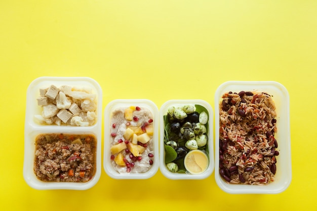 Plastic containers with delicious food over yellow surface