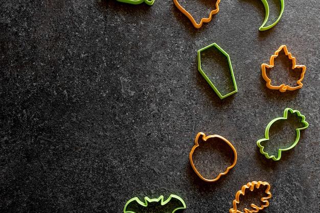 黒の背景にプラスチック製のクッキーカッターハロウィーンカボチャキャンディケインゴースト棺バット