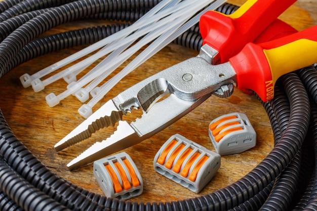 Пластиковая гофрированная труба для электромонтажа с помощью клещей и быстроразъемных клемм на деревянном столе в мастерской