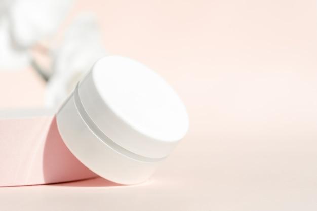 Plastic cream jar mockup on pink pedestal