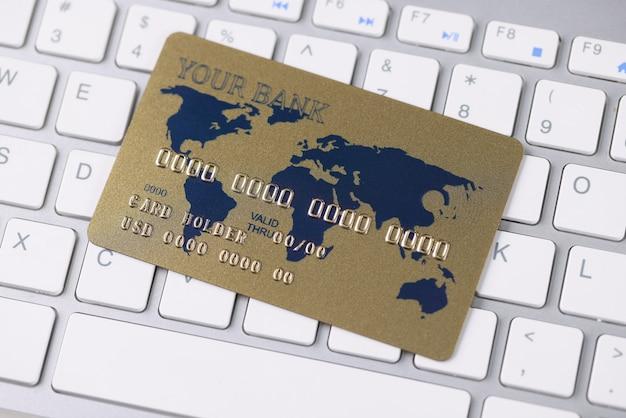 プラスチック製のクレジットバンクカードがキーボードにあります。オンライン決済の概念