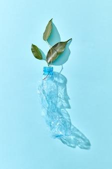 プラスチックのしわくちゃの空のボトルと緑の葉は、水色の壁に影のある枝、コピースペース。環境汚染の生態学的問題。