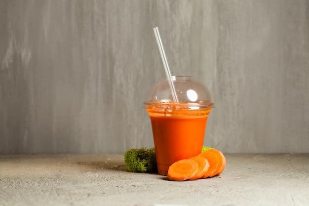 Пластиковый стакан морковного сока рядом со свежими овощами
