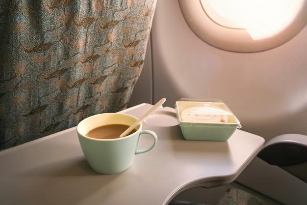Пластиковый стаканчик кофе с молоком и сладкий рулет на складном столике перед самолетом. концепция путешествия.
