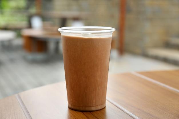 Пластиковый стаканчик вкусного прохладного напитка на деревянном столе