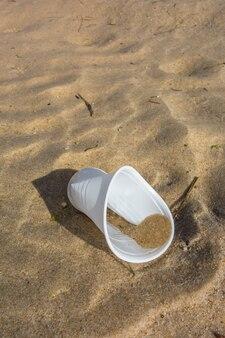 Пластиковый стаканчик на песке пляжа. пластиковое загрязнение концепции океанов.