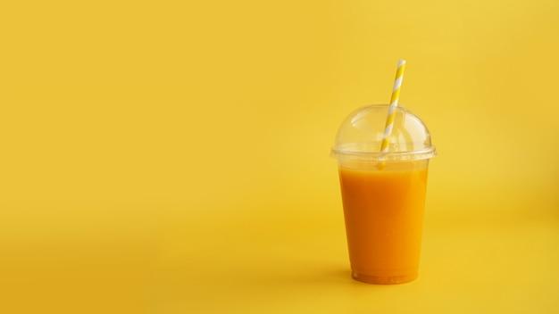 Plastic cup of orange drink natural juice or smoothies