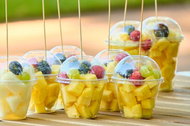 カウンターにパイナップルやブラックベリーなどのフルーツが入ったプラスチック製のコップ。