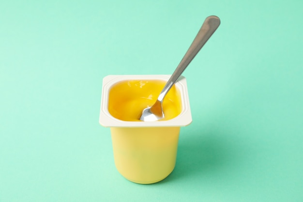 Plastic cup of yogurt with spoon on mint background