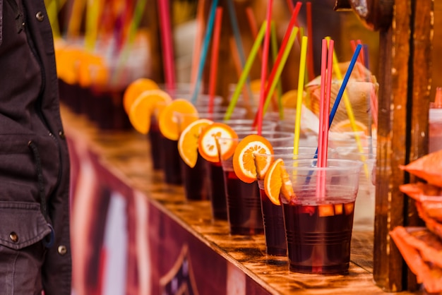 Plastic cups with refreshing alcoholic drinks with orange slices and colored straws at a summer festival.