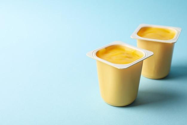 Plastic cups of yellow yogurt on blue background