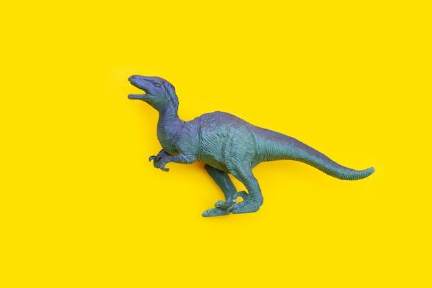 黄色の背景にプラスチック製の恐竜のおもちゃ。