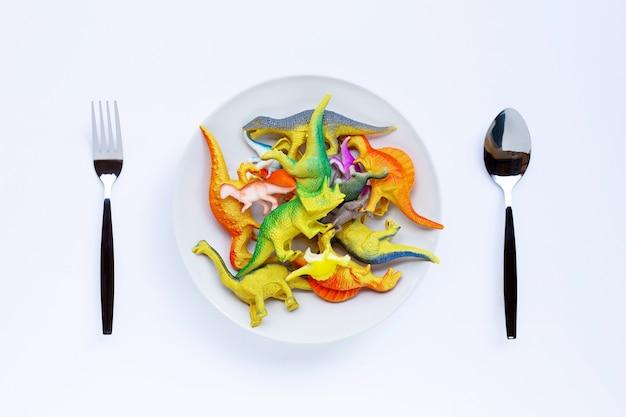흰색 표면에 포크와 숟가락 흰색 접시에 플라스틱 공룡 장난감