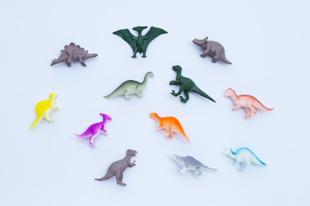 Plastic dinosaur toys on white background. top view