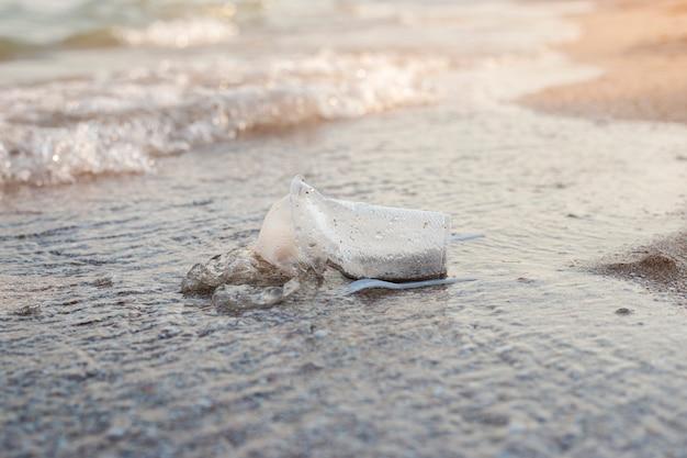 砂浜の背景にプラスチック皿とビニール袋。