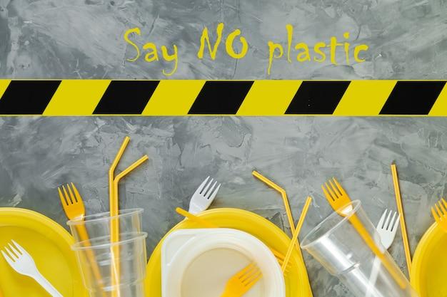 灰色の背景にプラスチック皿と警告テープ。スペースをコピーします。環境汚染。