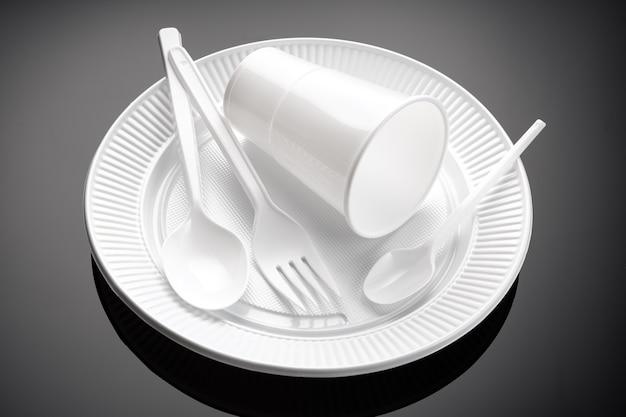 Пластиковая посуда. белая чашка, тарелка, вилка и ложка одноразовые пластиковые отходы