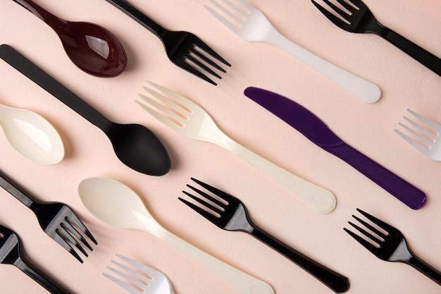 ピンクの表面にプラスチック製の使い捨てフォークスプーンとナイフ