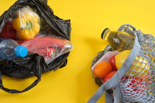 Пластиковая одноразовая упаковка по сравнению с многоразовой, без пластиковой концепции, сетчатый пакет и пластиковый пакет для продуктов на желтом фоне для копирования