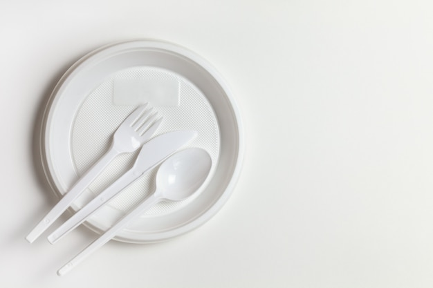 Plastic disposable white dishes, plate, spoon, knife, fork on white background