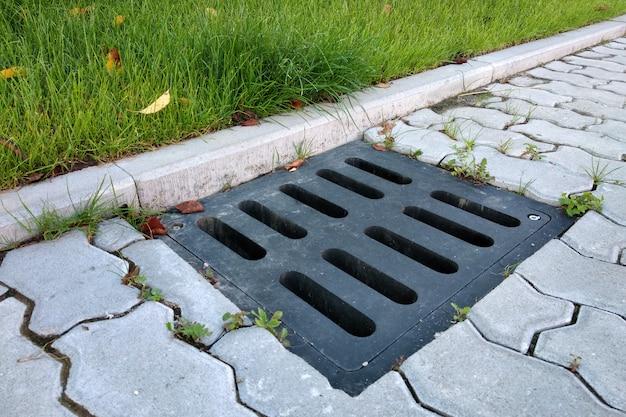 플라스틱 배수 홈통, 푸른 잔디 잔디밭 및 돌 포장 보도.