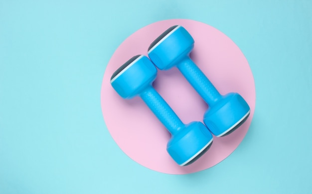 Пластиковые гантели на синем фоне с розовым пастельным кругом. вид сверху. минималистичная спортивная концепция. вид сверху