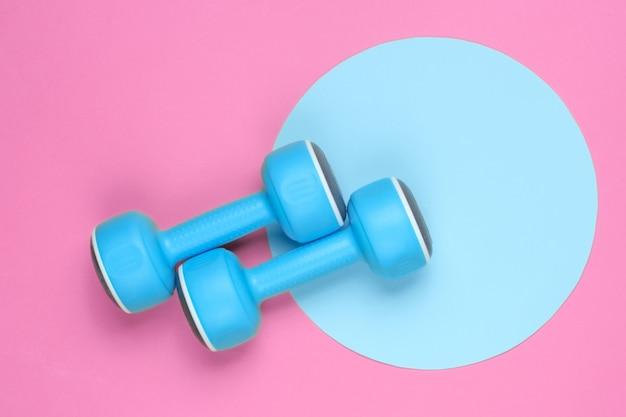 파란색 파스텔 원이 있는 분홍색 배경에 플라스틱 아령. 평면도. 최소한의 스포츠 개념입니다. 평면도