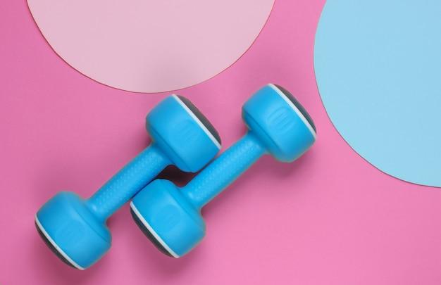 복사 공간을 위한 파란색 분홍색 파스텔 원이 있는 분홍색 배경에 플라스틱 아령. 평면도. 최소한의 스포츠 개념입니다. 평면도