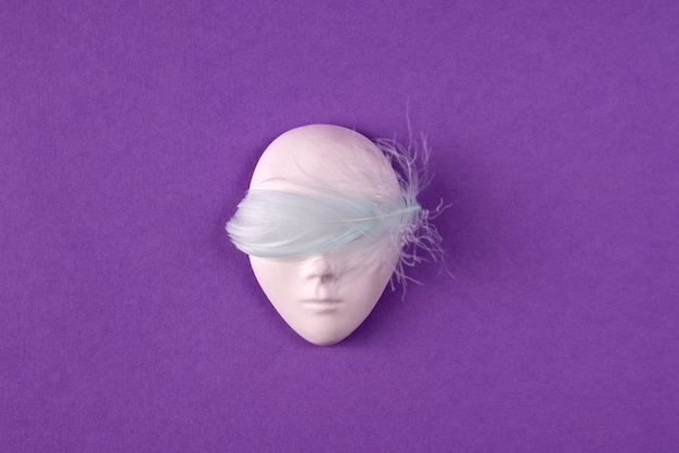 Plastic face mask decorated with light blue feather over it's eyes on purple background