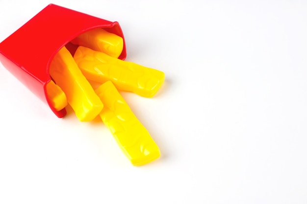 Пластиковый фаст-фуд, игрушка картофель-фри на белом фоне. нездоровый. не органический.