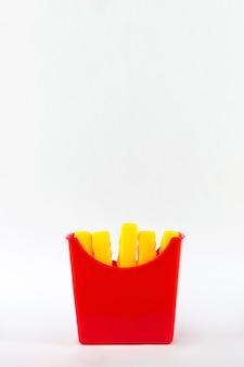 플라스틱 패스트 푸드, 장난감 플라스틱 감자 튀김, 흰색 바탕에 감자 튀김 장난감. 건강에 해로운.